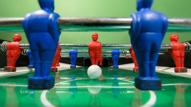 Close up view of Foosball table with ball positioned to be hit