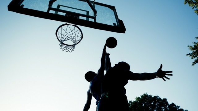 Silhouette of basketball players: one going for a layup while the other successfully blocks it